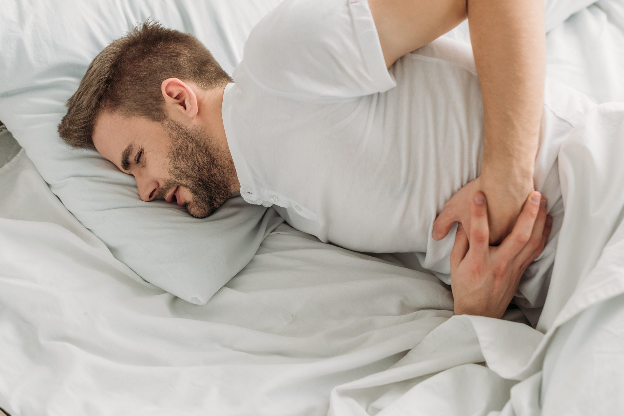 man laying in bed with stomach pain