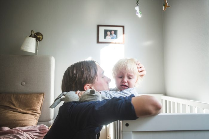 father consoling crying baby in crib at home