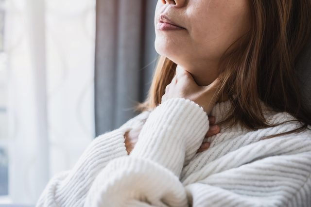 cropped shot of woman holding sore throat