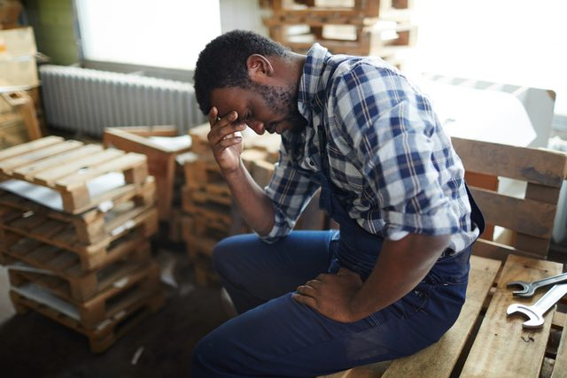 man suffering from a headache at work