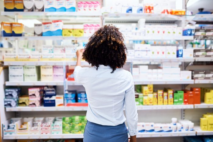 woman in drug store picking out medication to buy
