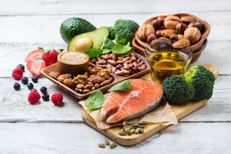 display of heart-healthy foods: salmon, fruit, veggies, olive oil, and nuts