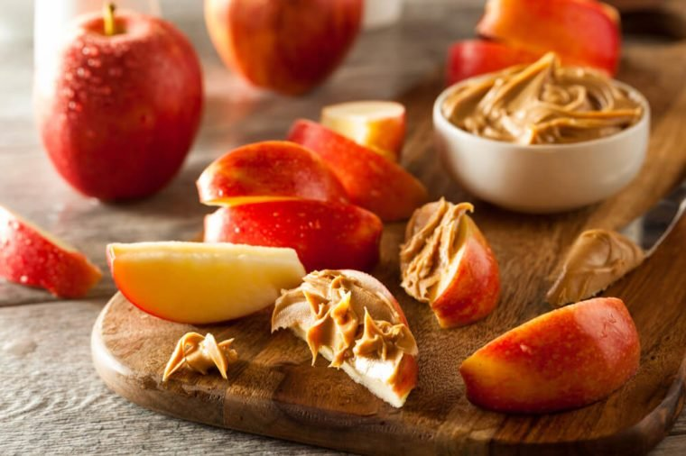 sliced and whole apples with peanut butter