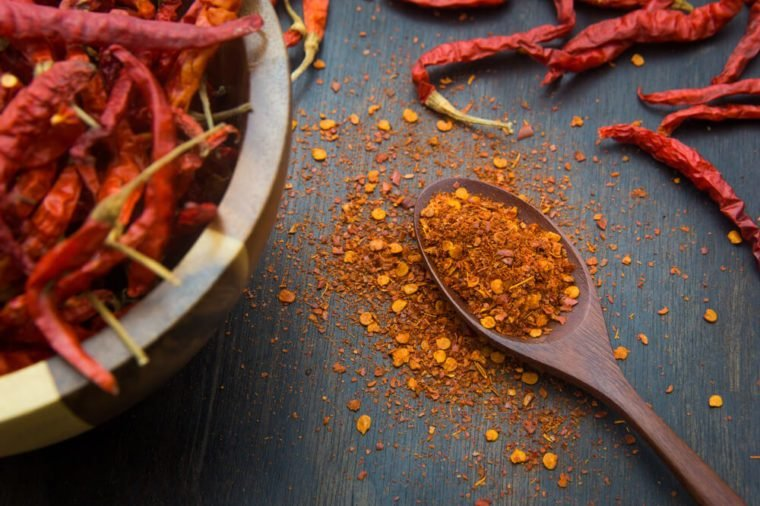 Cayenne pepper on a wooden spoon with bowl of whole peppers