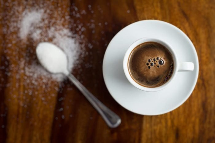 Cup of coffee with sugar on wooden table