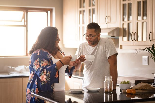 couple standing in kitchen talking and drinking coffee