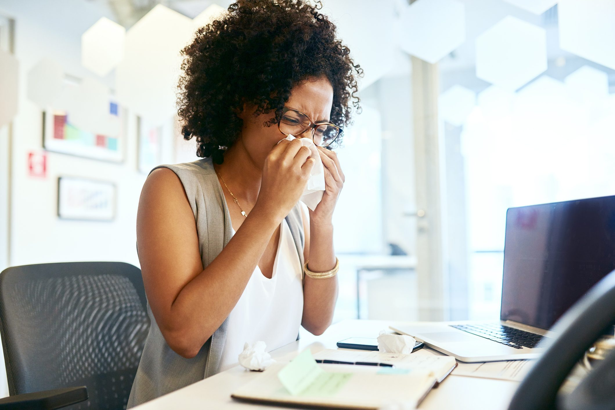 woman sneezing while working at desk
