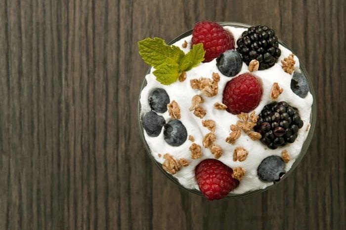 Yogurt parfait with fresh berries and a mint leaf