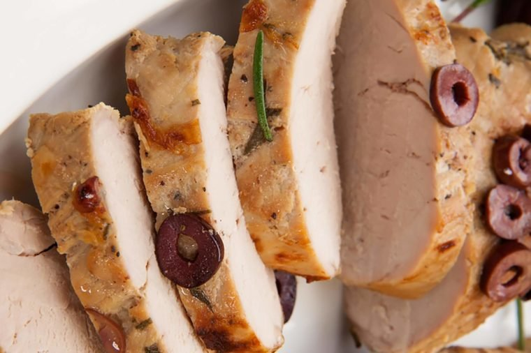 Closeup of delicious sliced roast pork tenderloin with olives.