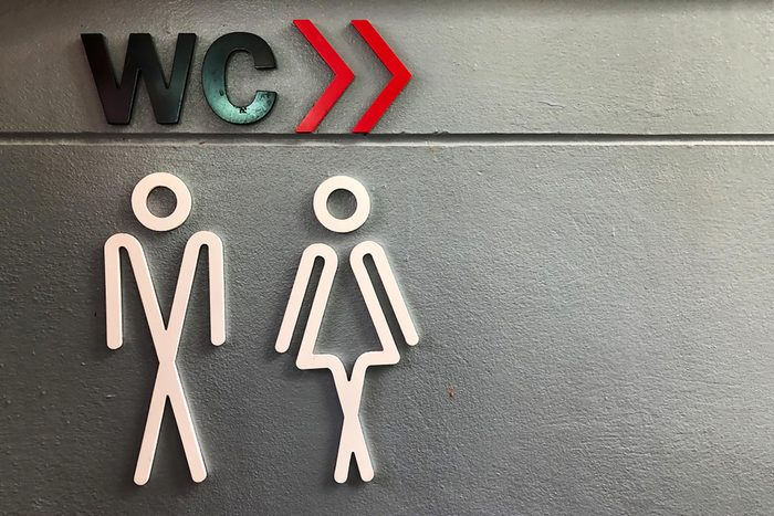 Toilet sign with gray background.