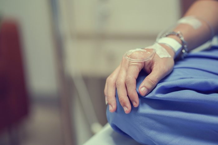 close up patient man hand with label and drip waiting for operation of chemotherapy medical , cancer day concept