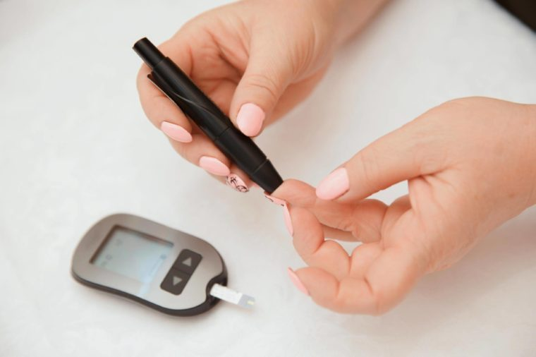 Woman pricking her finger to check blood sugar level.
