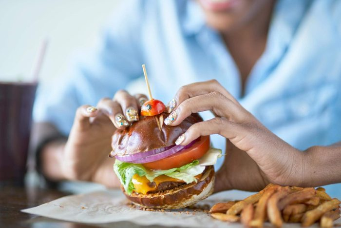 woman eating burger at restaurant