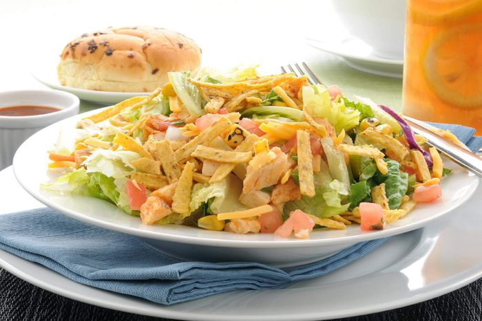 A taco salad with corn chip strips