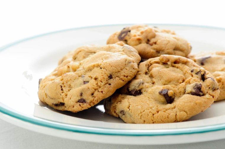 Oven fresh, homemade chocolate chip and walnut cookies on a plate.