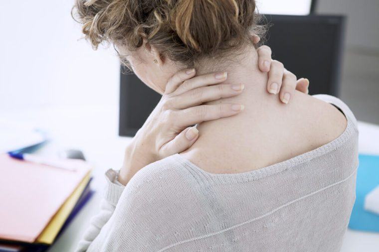 Woman holding her neck at the office.