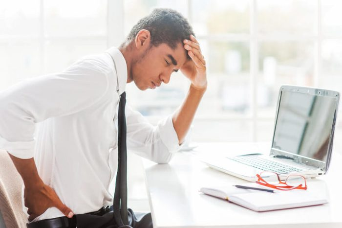 Man sitting at his desk holding his back as if in pain.