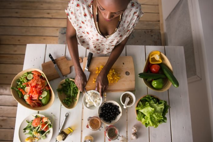 woman preparing meal with healthy food