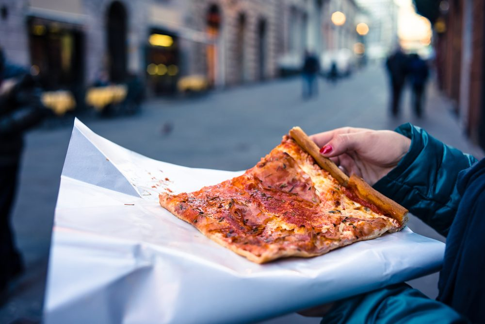 woman holding a square slice of pizza