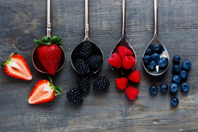 Strawberries, raspberries, blueberries and blackberries on vintage metal spoons over dark wood. Agriculture, Gardening, Harvest Concept. Background with space for text.
