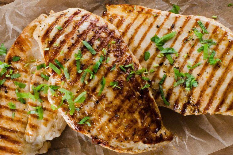 Grilled chicken breast on dark wooden background.
