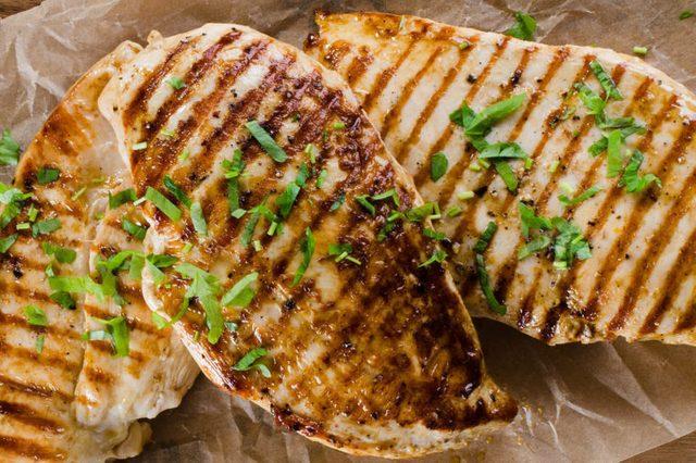 Grilled chicken breast on dark wooden background.