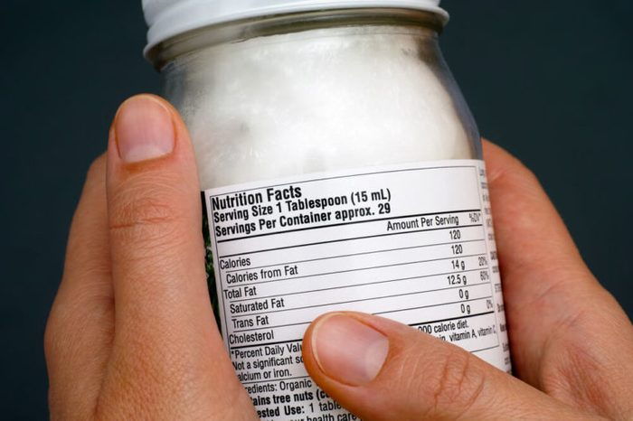 Reading a nutrition facts label on organic coconut oil jar