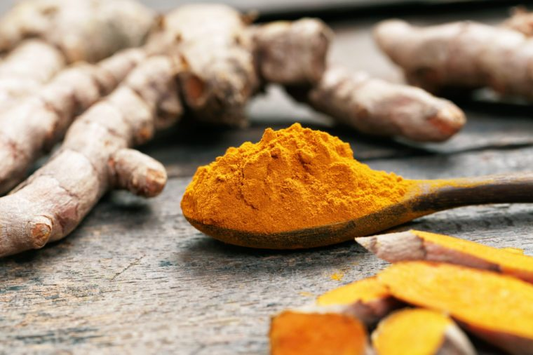 Turmeric powder on wooden spoon.