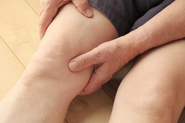 Older man holding his thigh and knee in pain.