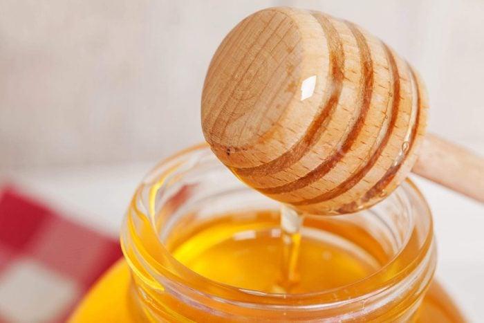Jar of honey with wooden honey dipper.