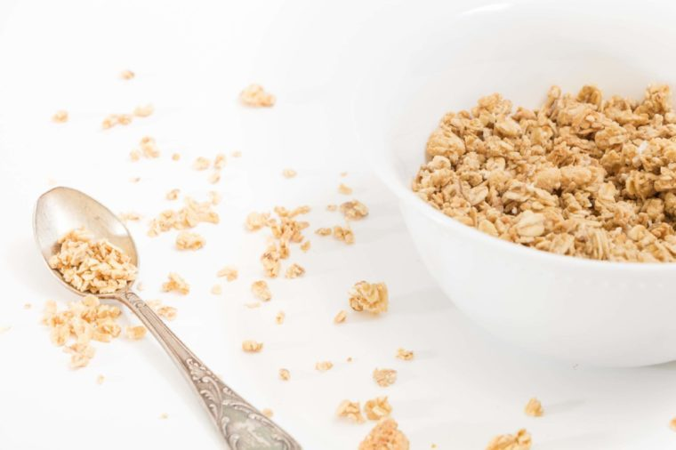 Bowl of granola and spoon on white background.