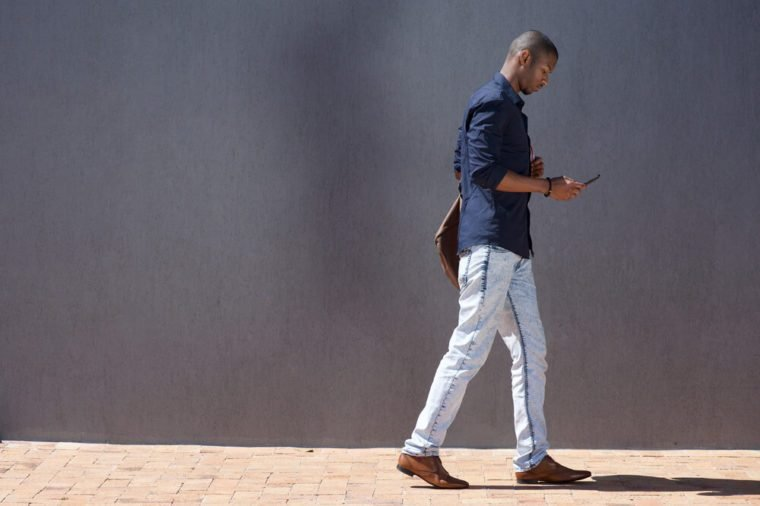Man walking while looking at smartphone