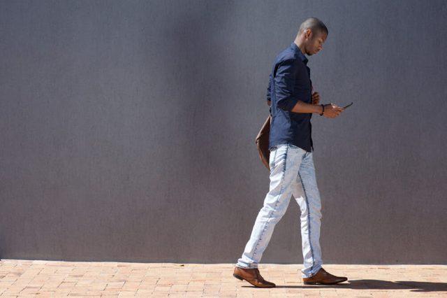 Man walking while looking at smartphone