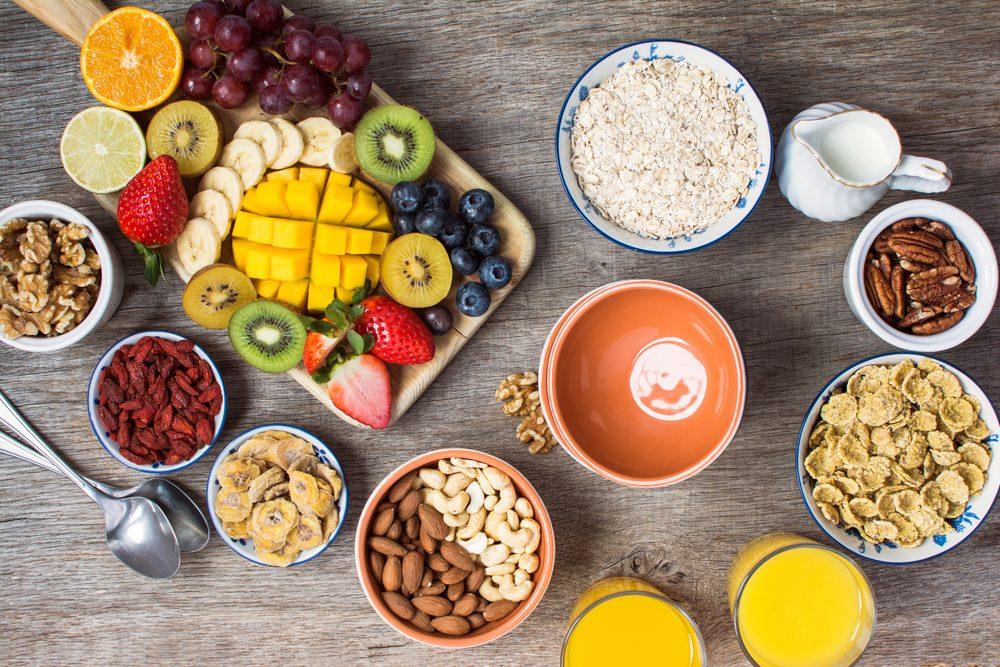 Healthy morning breakfast selection: cereals, nuts, orange juice, fruits, berries