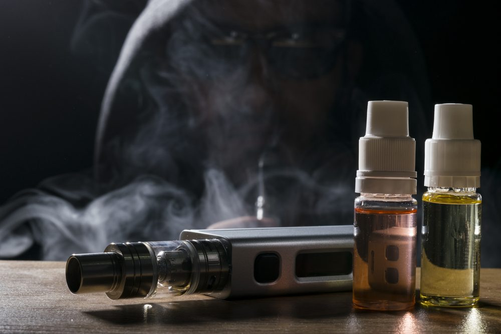 isolated vaping e liquid and vaping device for electronic cigarette on a dark background.