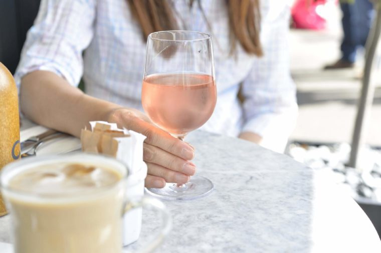 Woman's hand holding a glass of rose wine.