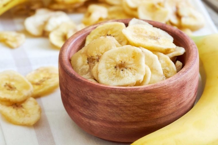 Bowl of dried banana chips in wooden bowl.