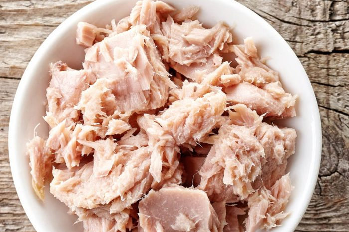 Bowl of canned tuna on wooden background.