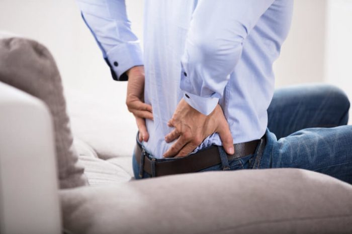 Man sitting on a sofa holding his back as if having pain.