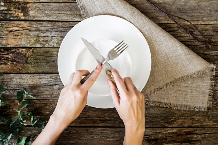 hands holding knife and fork over a plate