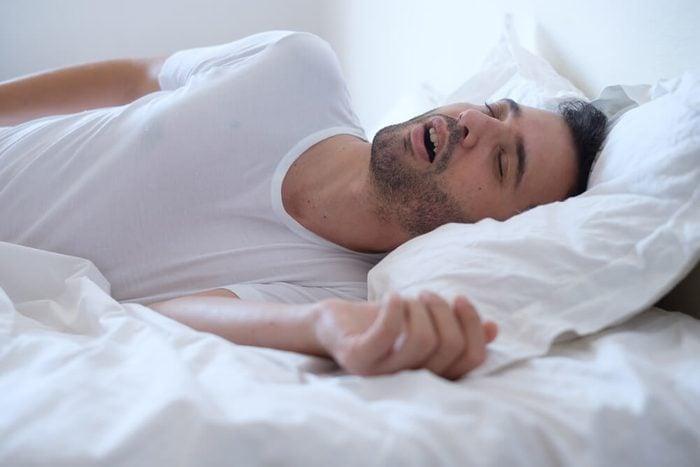 Man snoring because of sleep apnea lying in the bed