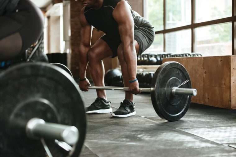 A person lifting a barbell at the gym.