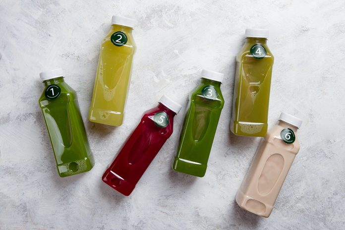 Healthy eating, drinks, diet and detox concept - close up of five plastic bottles with different fruit or vegetable juices for detox plan