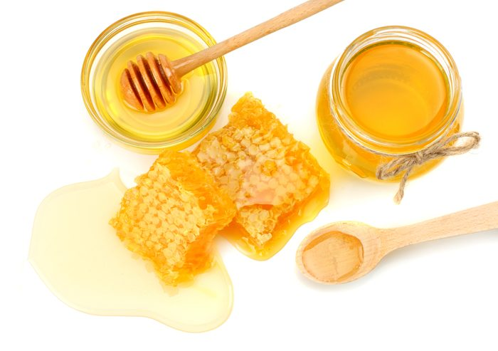 Honeycomb with honey dipper and honey isolated on white background. top view
