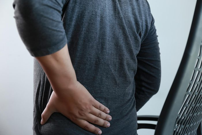 young man Feeling suffering Lower back pain Pain relief concept