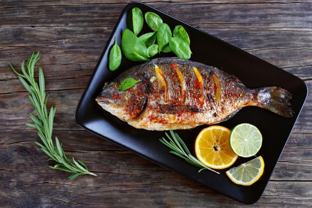 Roast fish with lemon and orange slices, spices, fresh rosemary and spinach