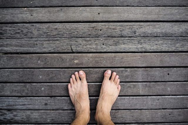 Bare feet standing on wooden floor