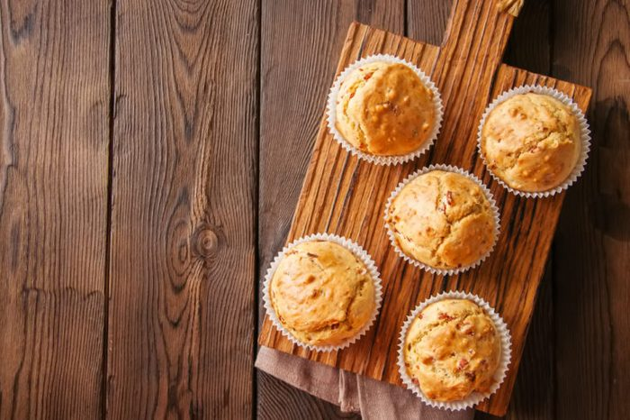 Homemade muffins with bacon and cheese on a wooden cutting board