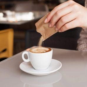 Woman hand adding sugar in coffee