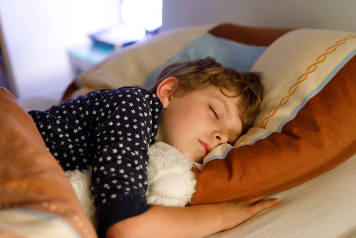 Little preschool kid boy child sleeping in bed with colorful lamp. School child dreaming and holding plush toy. Kid angry of darkness.